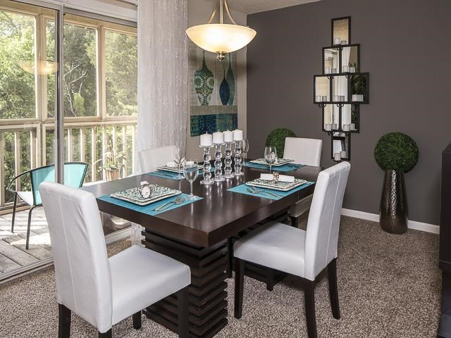 Model Dining Room with Set Table and White Chairs and Decorations on the Walls