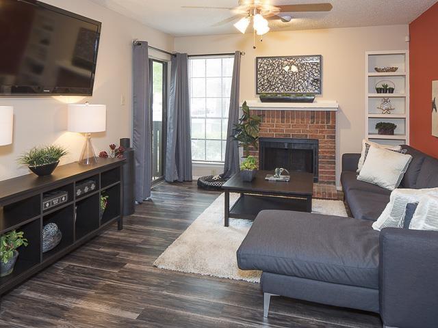 Model Living Room with Fireplace and Hardwood Style Flooring Couch Coffee Table Area Rug