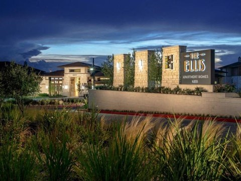 Evening shot of entrance with landscaping and road leading up to the clubhouse