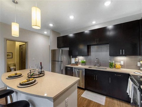 Fully equipped kitchen with double basin sink, espresso colored cabinets, chrome finished appliances, gourmet kitchen island, and hardwood style flooring
