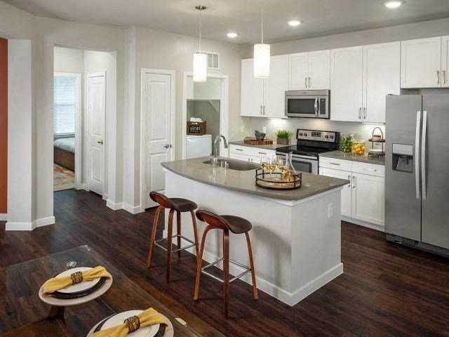 Fully equipped kitchen interior with chrome finished appliances, two bar stools paired with the kitchen island, and hardwood style flooring