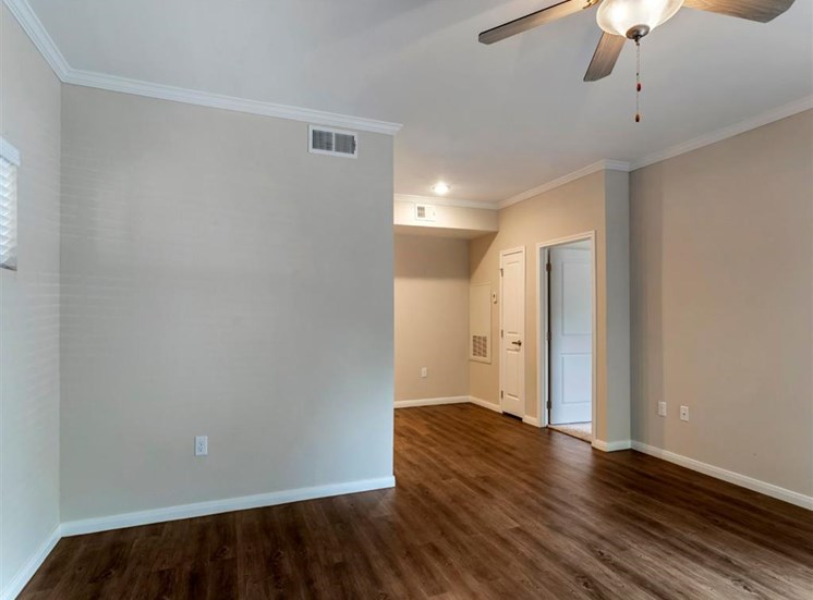 Living room space with hardwood style flooring, ceiling fans, tan walls, and white trim.