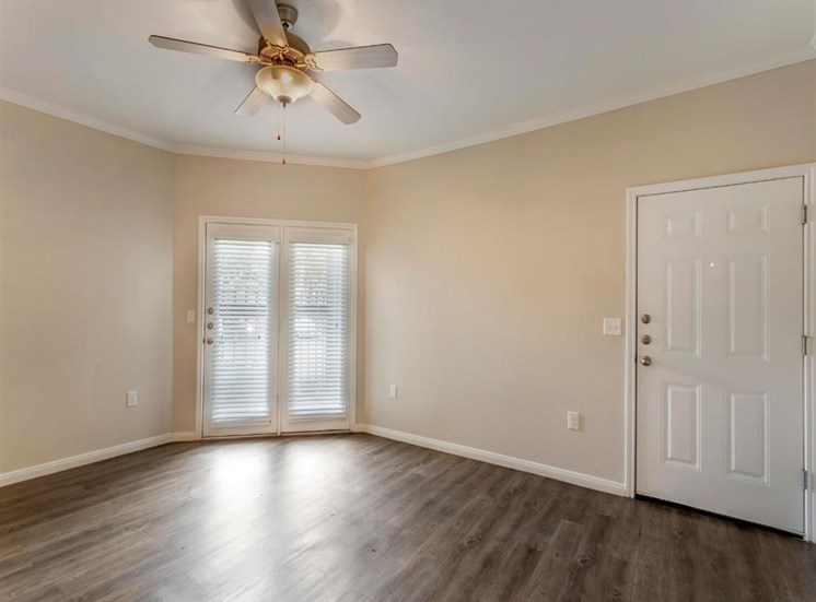 Living room view with hardwood style floors, tan painted walls, ceiling fan, and a view of the patio doors