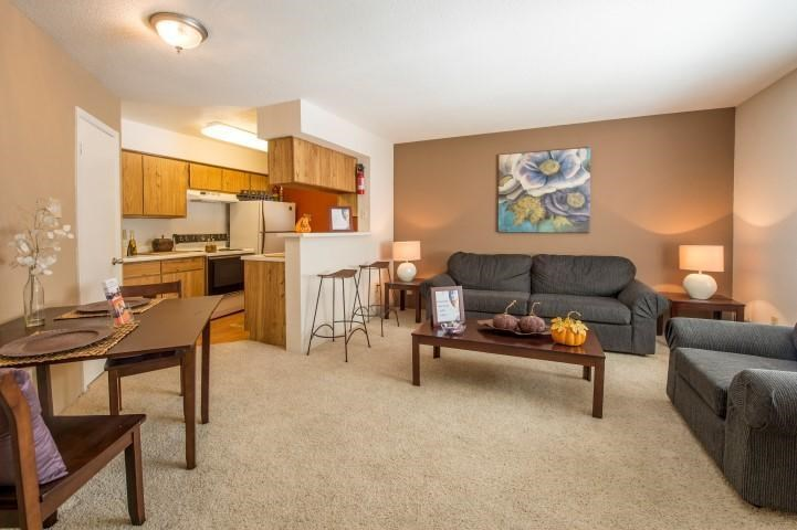 Open Carpeted Floor Plan with Couch, Coffee  Table, and Dinette Table Next to Kitchen with Breakfast Bar