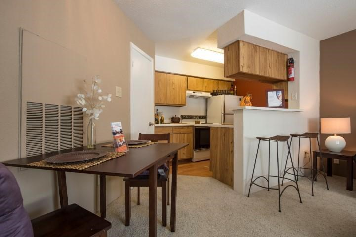 Open Carpeted Floor Plan with Dinette Table Next to Kitchen with Breakfast Bar