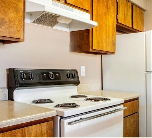 Kitchen with stove and refrigerator. Cabinets above all the appliances.