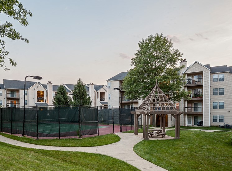 Enclosed Lighted Tennis Courts Next to Wooden Pergola in Front of Building Exterior