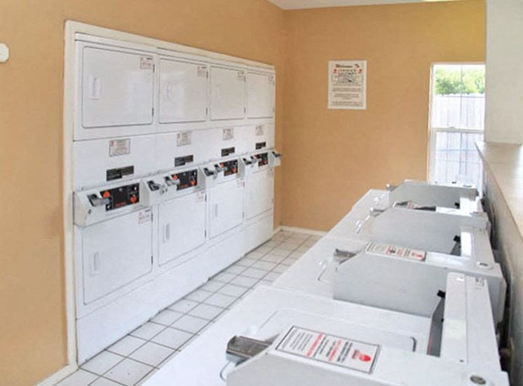 Laundry center with peach colored walls and multiple washer and dryers