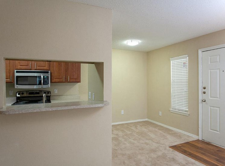 Kitchen and dining room area, hardwood style flooring directly in front of the door, then tan carpet in the remaining area, breakfast bar area, and tan painted walls