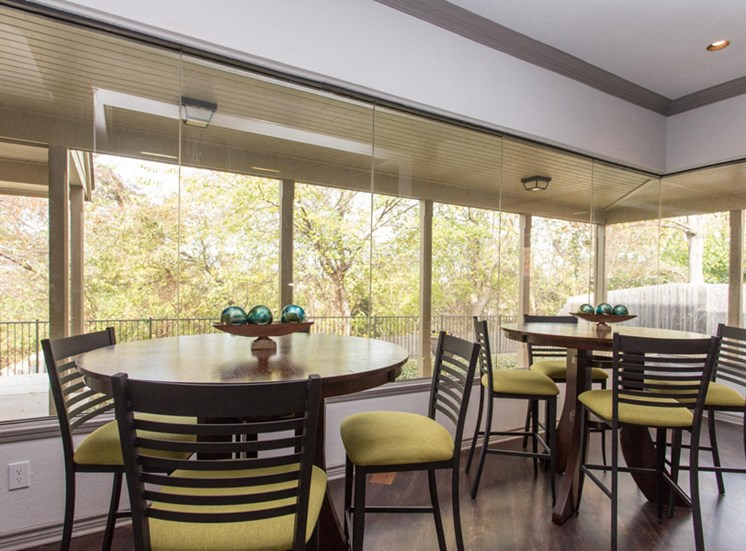 Resident lounge area with large windows with a scenic view, two round tables with paired chairs