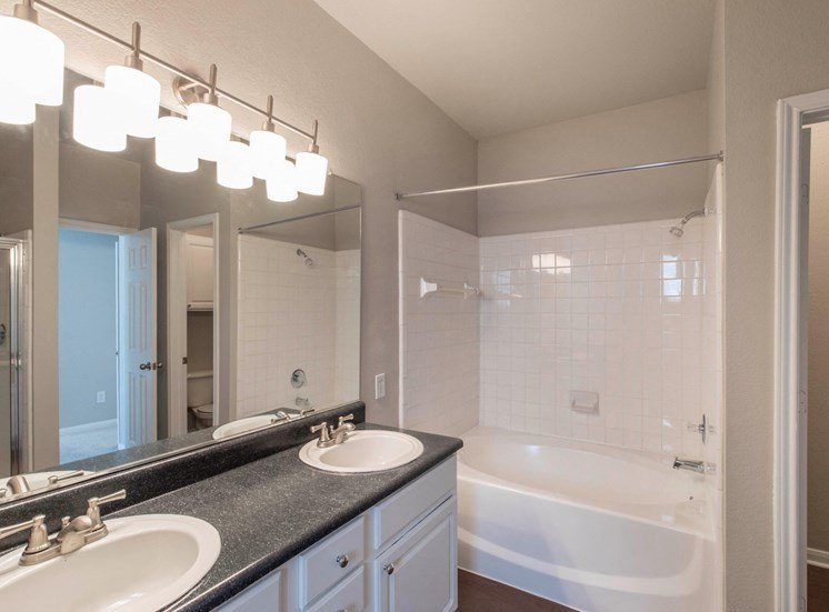 Large bathroom with vanity lights, double sinks, and garden style tub