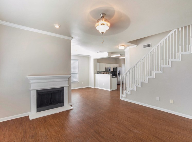Spacious living room with fireplace, hardwood style flooring, stairwell, and ceiling fan