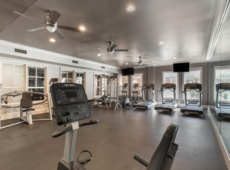 Fitness Center with treadmills, ceiling fans, and mounted televisions