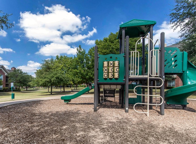 Outdoor playground with tick tack toe center, slide, ladder, and large space for running