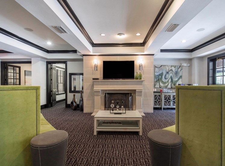 Clubhouse interior with dark carpet, green accent style couches, a fireplace, and a television mounted above the fireplace