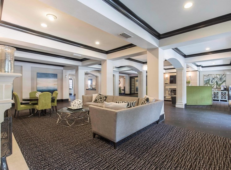 Clubhouse interior with black trim, white walls, green accent furniture, and dark brown carpet