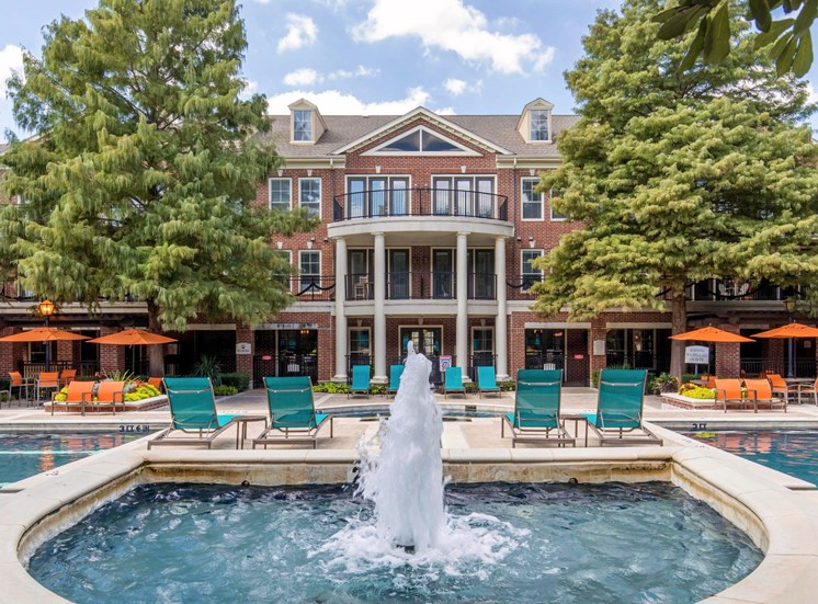 Fountain with pool side loungers and clubhouse exterior in the background