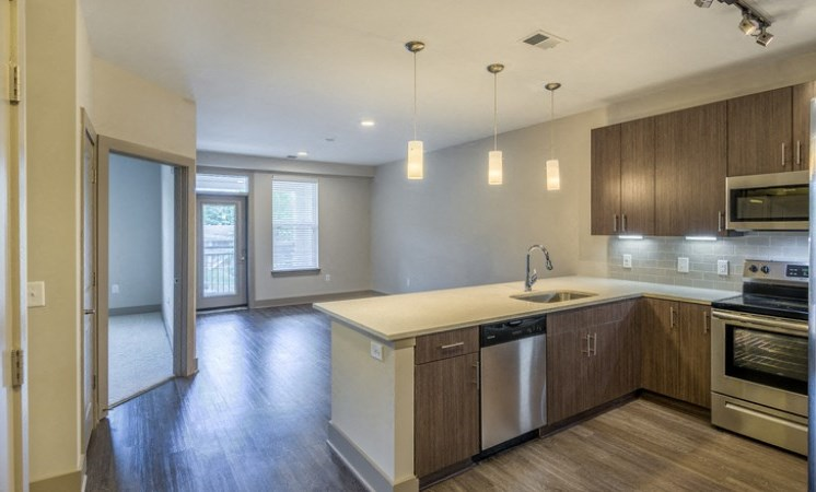 Kitchen with Open Layout and Breakfast Bar Wood Grain Cabinets and Stainless Steel Appliances and Living Room with Patio Door and Window