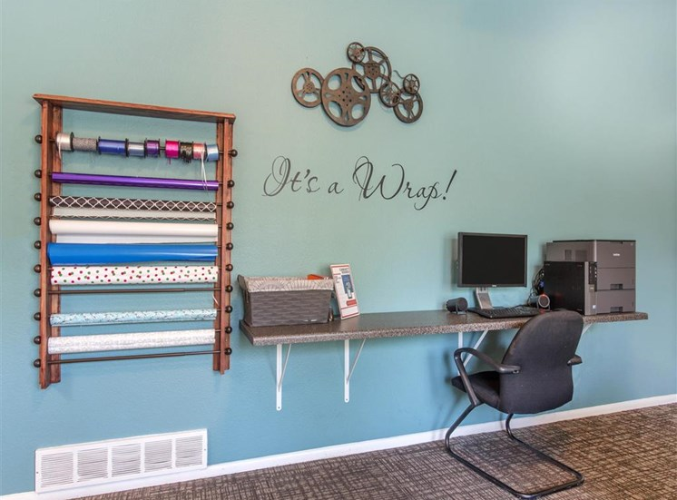 Gift Wrap Station with Wrapping Paper Roll Storage on Wall Next to Built in Counter with Chair and Computer