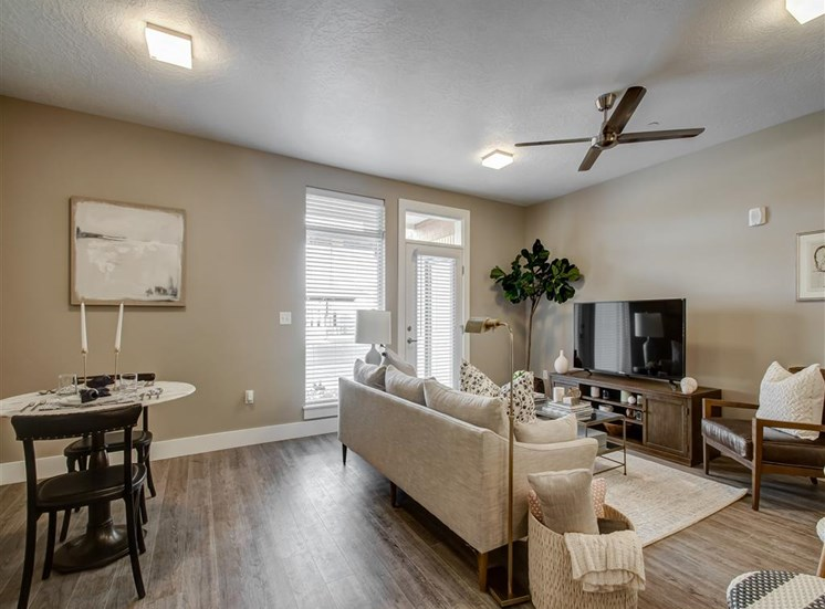 Model Living and Dining Room with Hardwood Style Flooring Dinette Table, White Couch, Entertainment Center  and Decorations