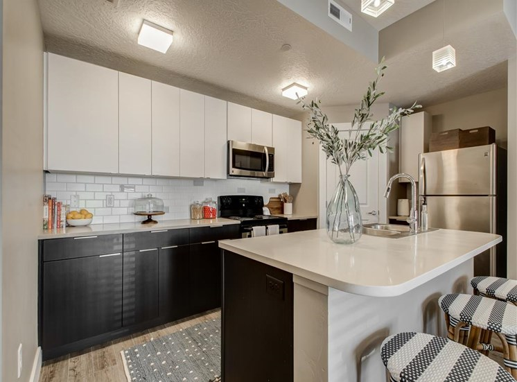 Model Kitchen with White Cabinets, White Counters, Stainless Steel Appliances, Decorations and Bar Stools