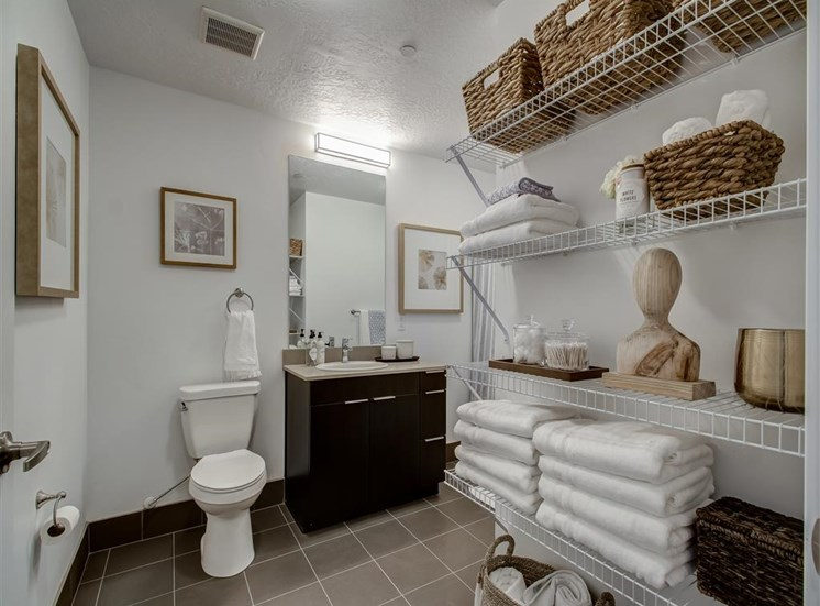 Model Bathroom with Wood Cabinets, Grey Counters, abd Wire Shelves with Decorations