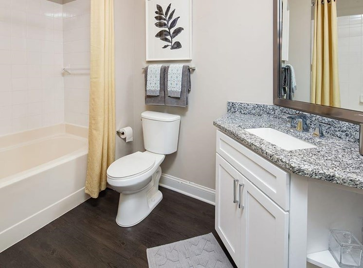 Bathroom with a tub shower. the vanity is in the corner of the bathroom. a towel rack sits above the commode