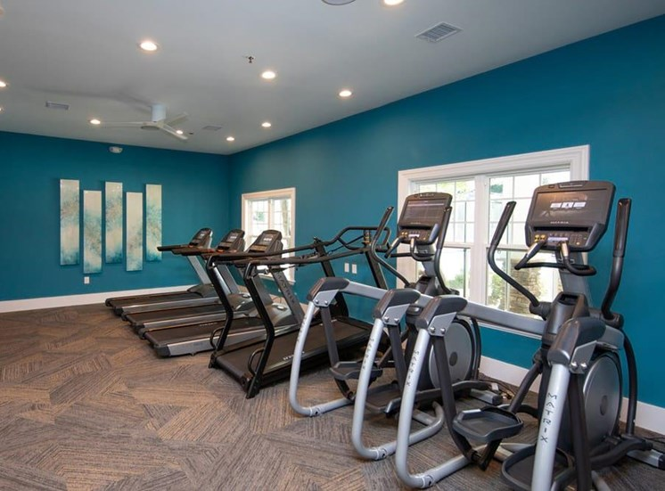 Fitness center with exercise equipment facing the wall with windows.