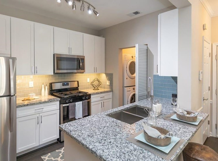 At the end of the kitchen is the door into the laundry room. The kitchen has stainless steel appliances and built in microwave, into the white cabinets.