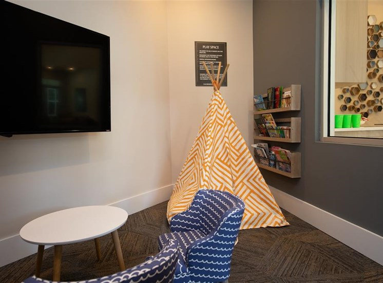 A small play area with a child table  with chair facing a tv on the wall. on the other side has a book shelf with a  teepee in front of it.