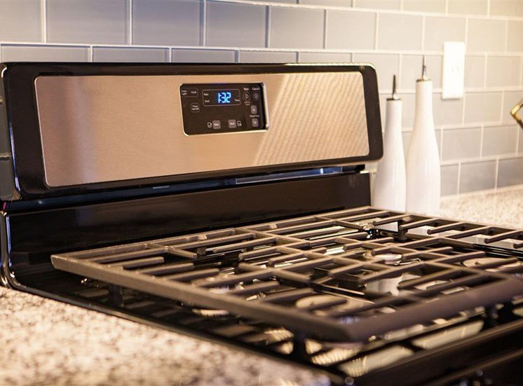 Stainless steel stove with a gray colored backsplash