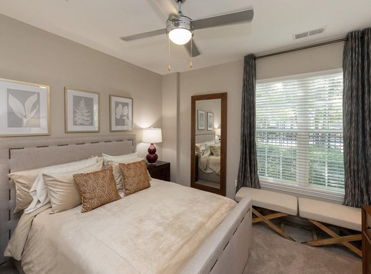Bedroom with queen size bed with night stands with lamps on both sides of the bed. a full size mirror is next to the night stand  large window with a bench in front of the window. There is a ceiling fan above the bed.