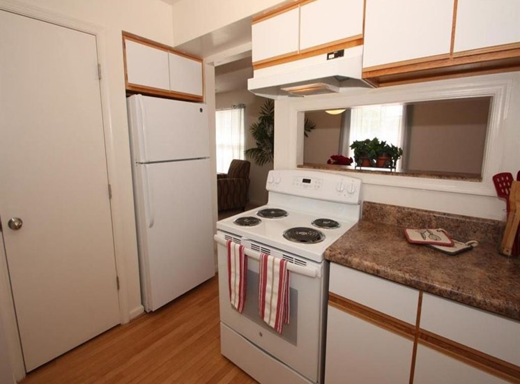 Kitchen with stove and refrigerator. Pantry door. Window style view above the stove looking towards the living room