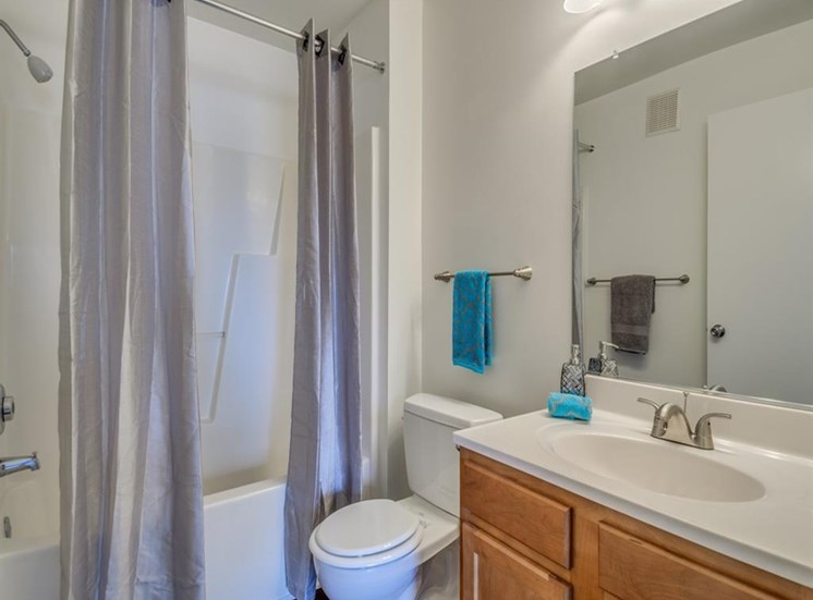 Bathroom with blue shower curtain, teal hand towels and wood cabinets