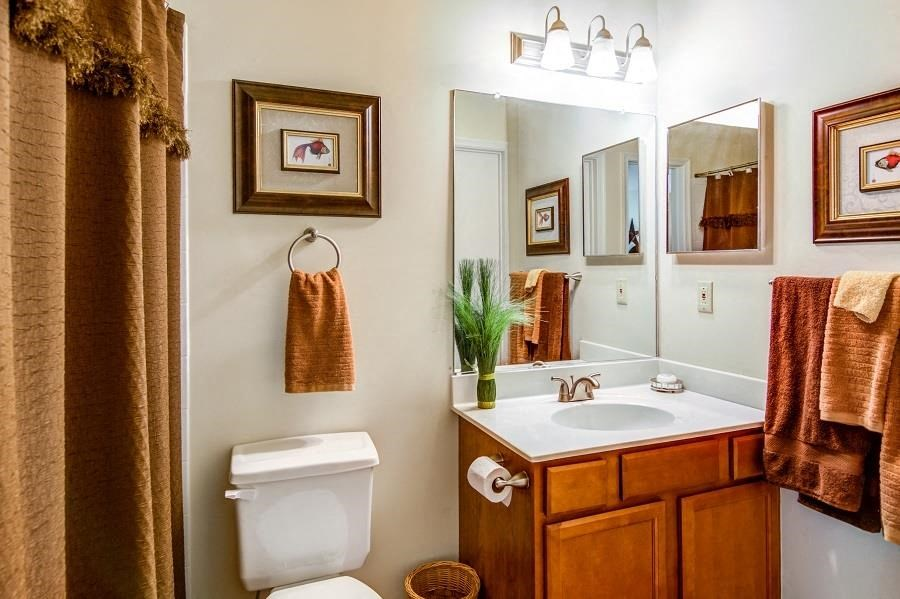 Model Bathroom with Brown and Tan Decorations Wood Cabinets and White Counters
