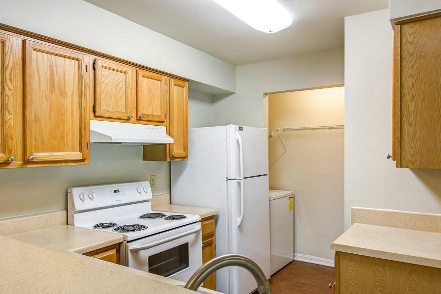 L Shaped Kitchen with Blonde Cabinets Tan Counters and White Appliances with Laundry Closet with Washing Machin