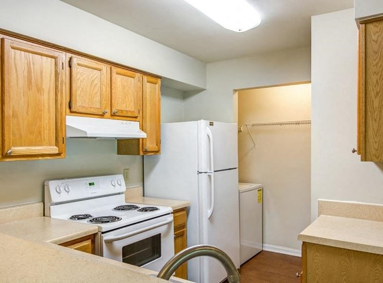 L Shaped Kitchen with Blonde Cabinets Tan Counters and White Appliances and Utility Closet with Washer Visible in the Background