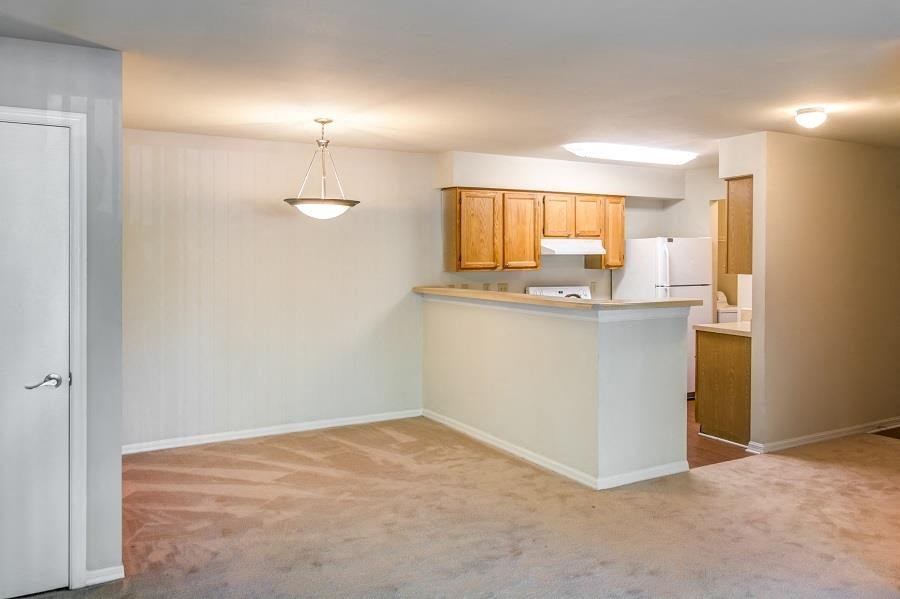 Open Floor Plan with Carpeted Dining and Living Room and Kitchen with Breakfast Bar Blonde Cabinets and White Appliances