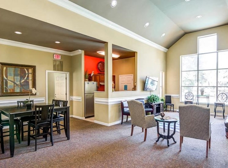 Clubhouse Seating Area with Large WIndows Next to Dining Table and Chairs by Clubhouse Kitchen with Red Accent Wall