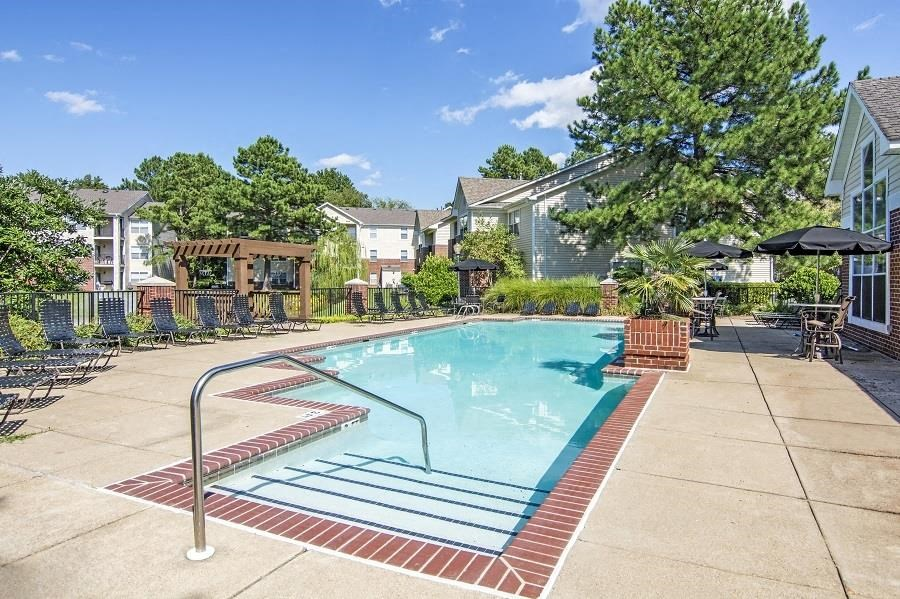 Swimming Pool and Sun Deck with Lounge Chairs Pergola and Tables with Umbrellas and Chairs Near Treeline