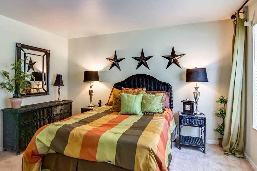 Model Bedroom with Bed Nightstand Dresser and Mirror and Metal Stars on Wall