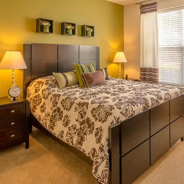 Model Bedroom Close up of Bed with Nightstands and Decorations on Green Accent Wall Behind Bed