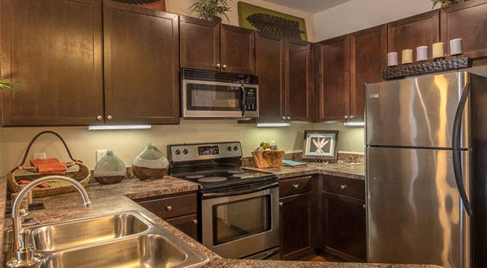 Kitchen with Brown Cabinets Stainless Steel Appliances Double Sink and Grey Counters with Decorative Items