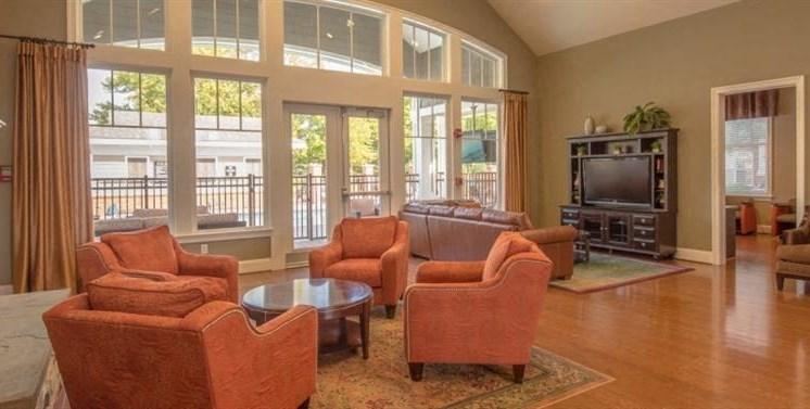 Clubhouse Seating Area with Salmon Chairs Around Round Coffee Table in Front of Fireplace with TV in Entertainment Center with Couch  in the Background