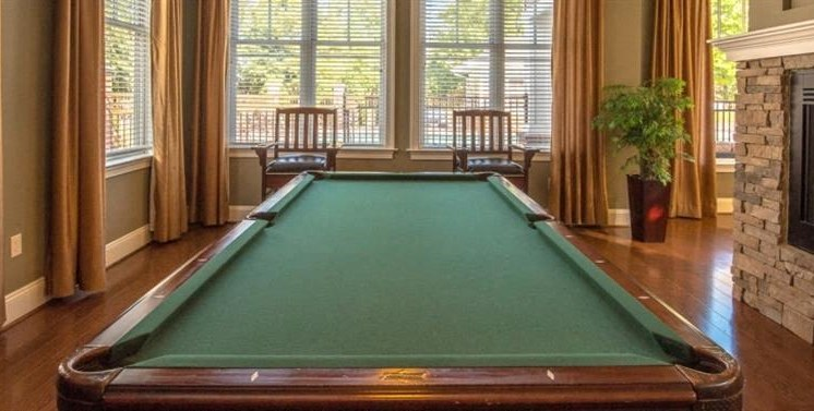 Billiards Table with Yellow Curtained Windows Brick Fireplace  and Wooden Chairs in the Background