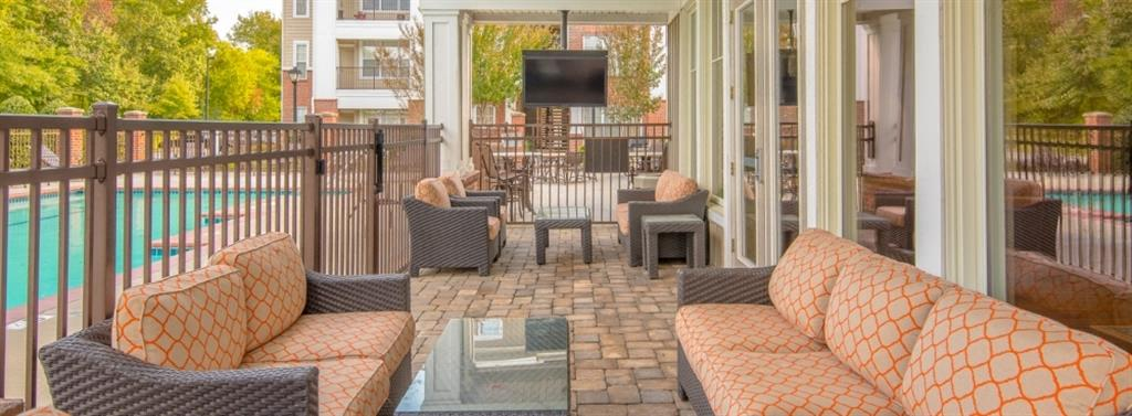 Poolside Deck with Cushioned Patio Couches and Glass Tables Next to Gated Pool Entrance