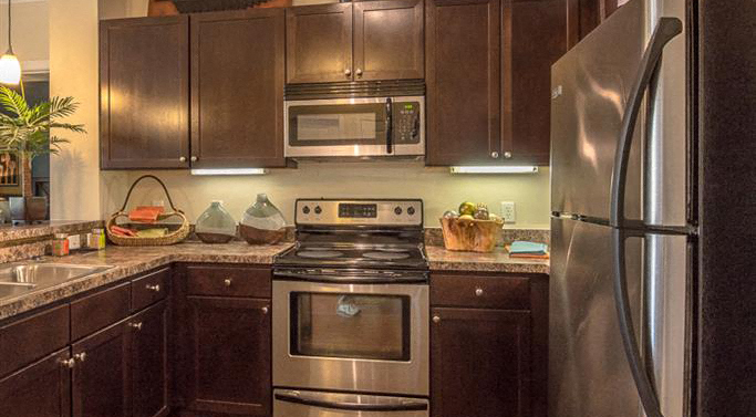 Kitchen with Brown Cabinets Stainless Steel Appliances and Grey Counters with Decorative Items