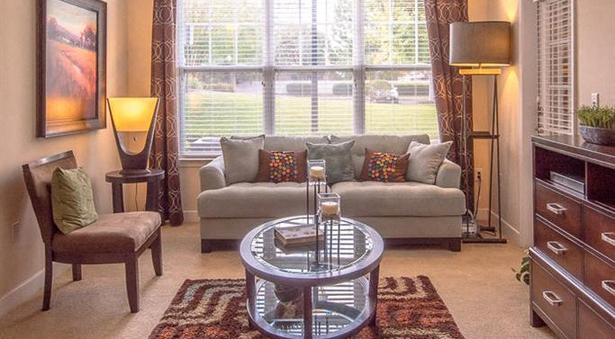 Model Living Room with Grey Couch with Throw Pillows in Front of Large Window with Chest of Drawers with Glass Coffee Table Nearby Across from Table Chair