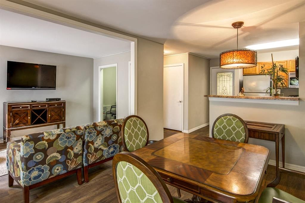 Model Floor Plan with Wooden Dining Room Table Green and White Chairs Couch TV and Entertainment Center and Kitchen with Stainless Steel Appliances and Blonde Cabinets Behind Breakfast Bar