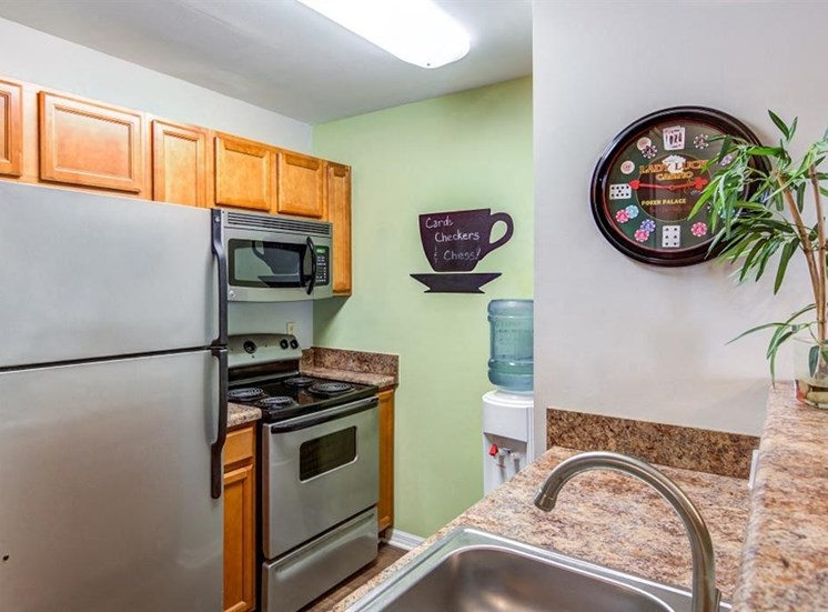 Kitchen with Blonde Cabinets and Stainless Steel Appliances with Beige Counters and Water Cooler Next To Coffee Cup Decoration on the Wall